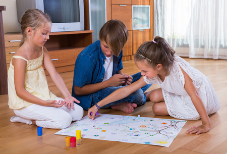 game board: Children sitting on floor at home with board game and dice