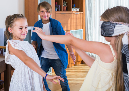 romp: smiling american children playing at Blind man bluff indoors