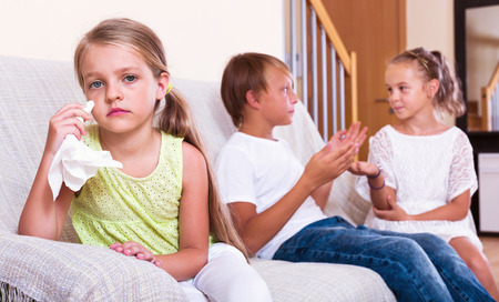 banter: Little  upset girl is jealous sister of stepbrother indoors Stock Photo