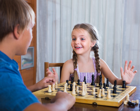 playing  chess: Brother teaching happy smiling little sister chess game at home
