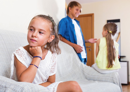 morose: Upset morose girl is jealous sister of stepbrother indoors Stock Photo