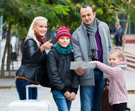 clase media: familia de clase media de cuatro miembros feliz dirección de verificación en el mapa de la ciudad