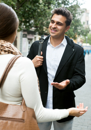 sidewalk talk: Asian man chasing smiling girl and making offers outdoor Stock Photo