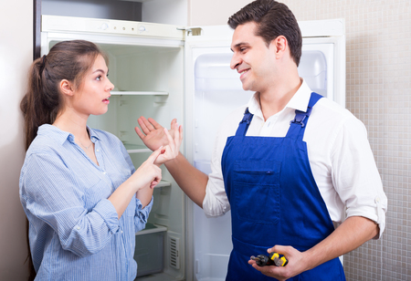 complaining: Worried  female complaining to handyman on problems with refrigerator Stock Photo