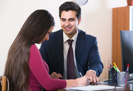 russian woman: Banking agent listening to young european customer and smiling in agency Stock Photo