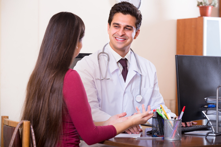 the doctor: Doctor positivo que recibe paciente enfermo en la oficina y el cuestionamiento Foto de archivo