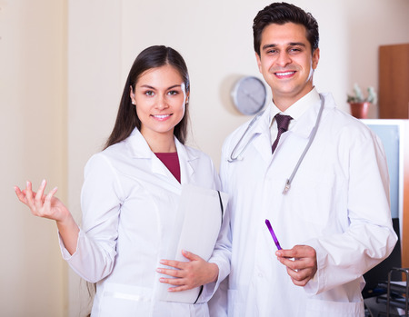 a lady doctor: Portrait of cheerful therapeutist and his young assistant in private clinic