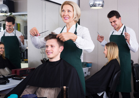 19's: Smiling senior woman hairdresser serving teenager in chair
