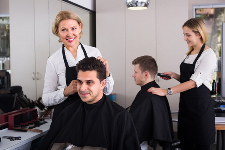 16s: Elderly blonde woman cutting hair of Indian guy in barbershop and smiling. Focus on guy