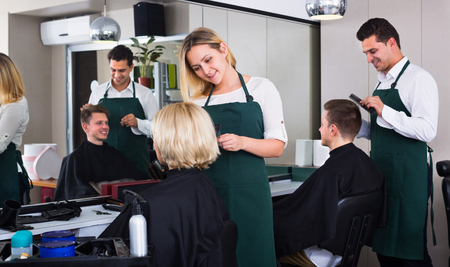 haircutter: Smiling young woman cutting female pensioner hair in hairdressing saloon
