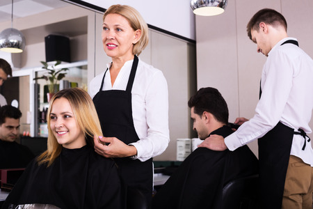 16s: Mature woman cuts hair of blonde girl in the beauty salon. Focus on girl