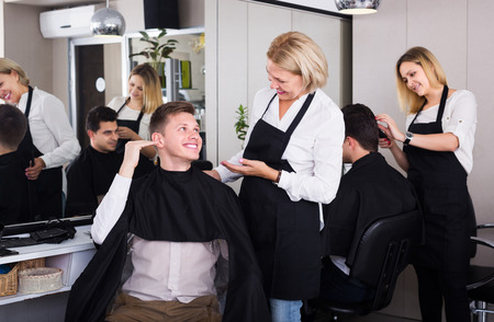 19's: Happy senior hairdresser serving teenager guy in chair