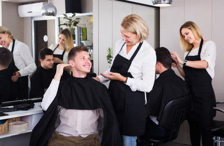 19's: Happy senior hairdresser serving teenager guy in chair