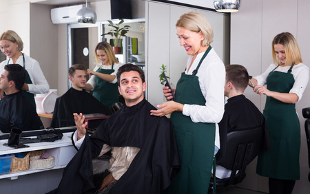 19's: Smiling elderly woman cutting hair of brunet guy in barbershop Stock Photo