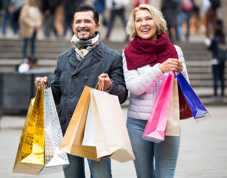 mature couple: Portrait of happy smiling mature couple chasing streets in shopping tour Stock Photo