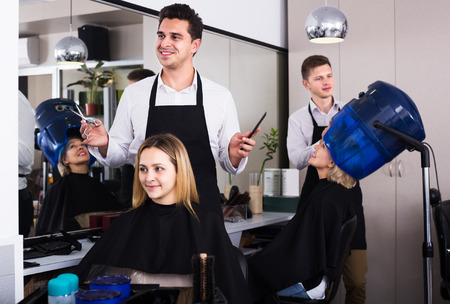 18's: Professional hairstylist cuts hair of blonde girl at the beauty salon