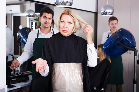 badly: Furious mature woman screaming on hairdresser as hair cut badly Stock Photo