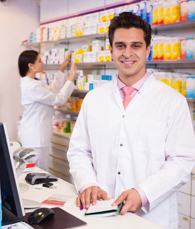 farmacy: Portrait of positive pharmacist and assistant working at farmacy reception