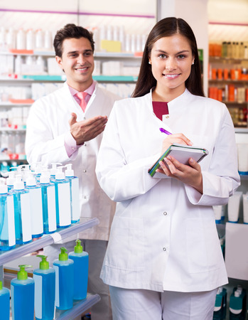 farmacy: Portrait of two young friendly pharmacists working in modern farmacy Stock Photo