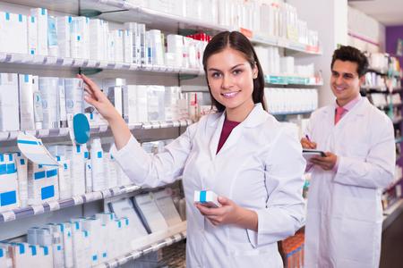 farmacéutico positivo y técnico de farmacia que presenta en la farmacia Foto de archivo