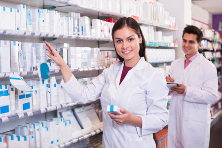 pharmacy pills: Positive pharmacist and pharmacy technician posing in drugstore