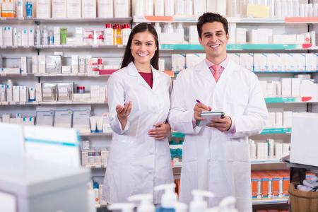 pharmacist: Positive pharmacist and pharmacy technician posing in drugstore