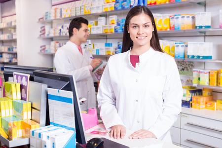 farmacéutico alegre que se coloca en el escritorio de pago y técnico de farmacia ayudar Foto de archivo