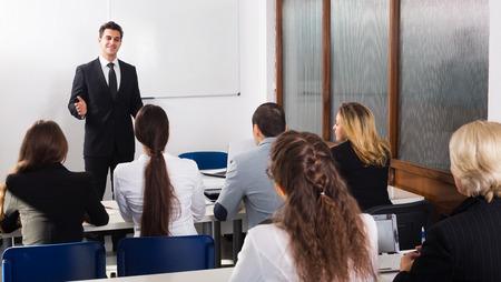 Gelukkig jonge professor en professionals op uitbreiding business courses