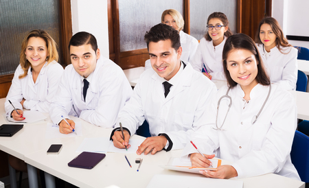25s: Group of scientists in white uniform at advanced training courses. Focus on man