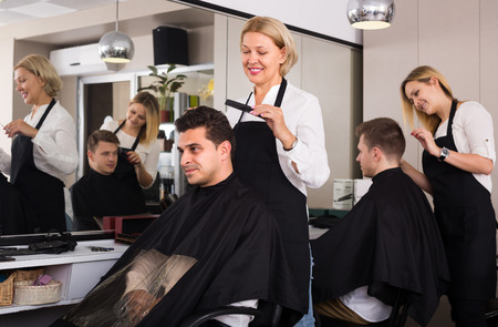 16s: Smiling elderly blonde woman cutting hair of Indian guy in barbershop Stock Photo