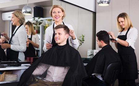 19's: Positive senior hairdresser serving teenager in chair