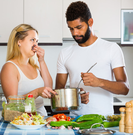 interracial family: Portrait of interracial family couple with stinking meal in kitchen