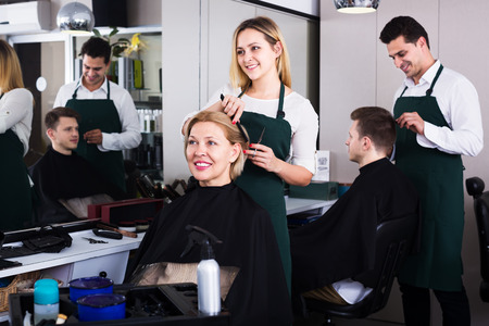 18's: Positive blonde cuts hair of mature woman at salon Stock Photo