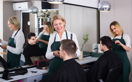 peignoir: Mature hairdresser cutting hair of male teenager Stock Photo