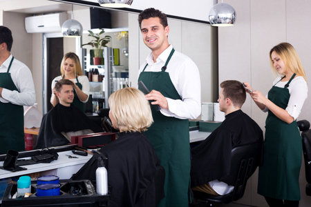 18's: Attractive professional stylist cutting hair of elderly blonde in salon Stock Photo