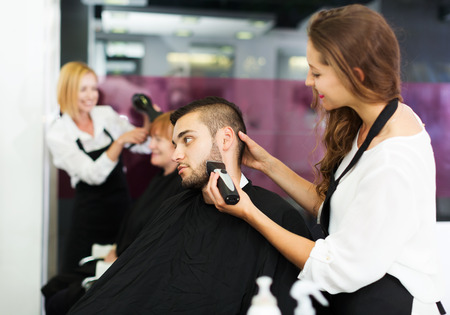 haircutter: Haircutter makes the haircut for young man in the hairdressing salon