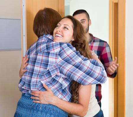 threshold: Mother greeting happy young couple at threshold
