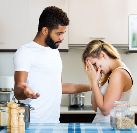 girl fighting: Sad young guy and white crying girl fighting in domestic kitchen