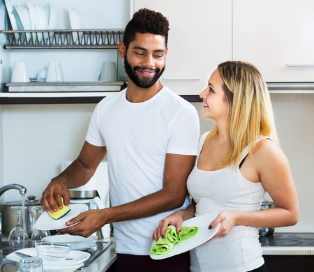 spouses: Happy interracial spouses cleaning in the kitchen together and smiling