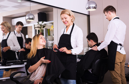 19's: Senior woman cuts hair of blonde girl at salon. Focus on girl