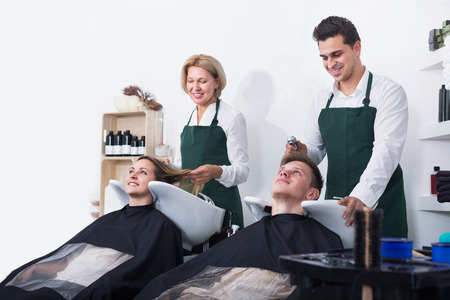 19's: Portrait of pleased customers and hairstylers washing hair in salon Stock Photo