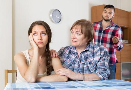 sullen: Mature woman comforting sullen daughter  in living room Stock Photo