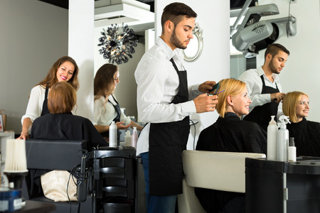 haircutting: Male barber with scissors in his hands is making a haircut for a woman sitting on a chair in a salon