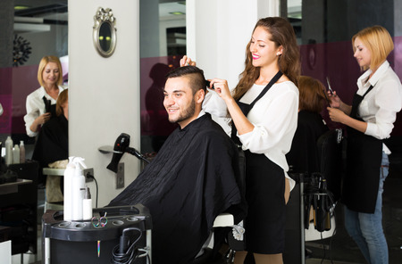 scissors hair: Happy guy cuts hair at the hair salon Stock Photo
