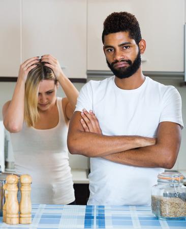 interracial family: unhappy european interracial family couple with serious faces quarrelling in kitchen. focus on man