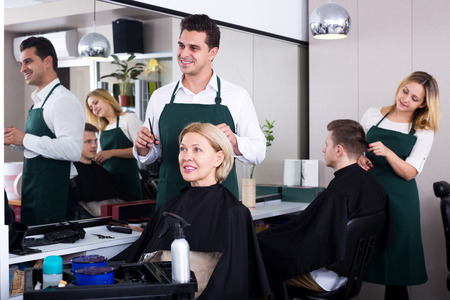 18's: Positive male stylist cutting hair of elderly blonde in salon