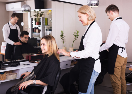 19's: Mature woman cuts hair of blonde girl at salon. Focus on hairdresser Stock Photo