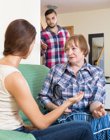 sullen: Mother comforting sullen daughter in living room