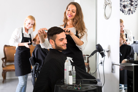 Beautiful young hairdresser working in a salon is making a haircut for a handsome man Foto de archivo