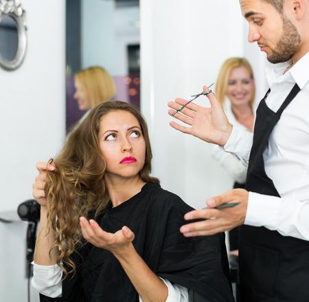 haircutter: Haircutter quarrels with the client in the barbershop Stock Photo